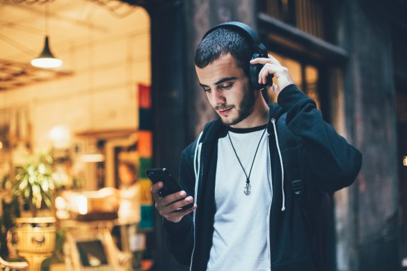 Male in front of shop with wireless headphones